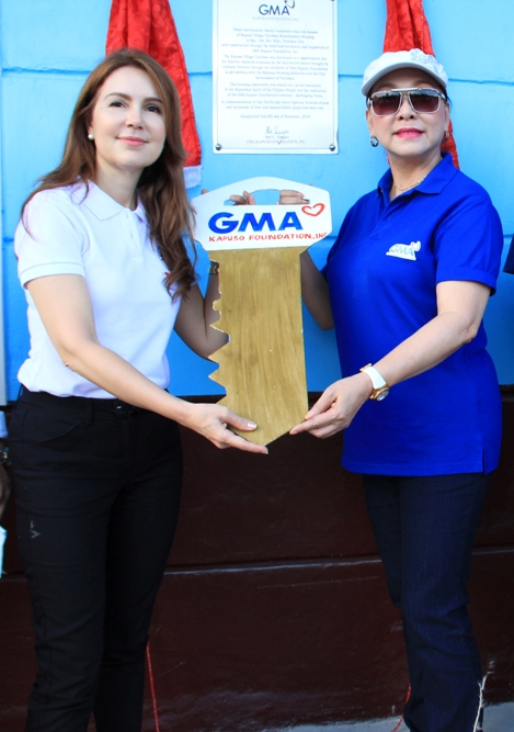 City Councilor Cristina Gonzales-Romualdez representing the City Government of Tacloban receives the ceremonial key to the Kapuso Village Tacloban from GMAKF EVP and COO Mel C. Tiangco.